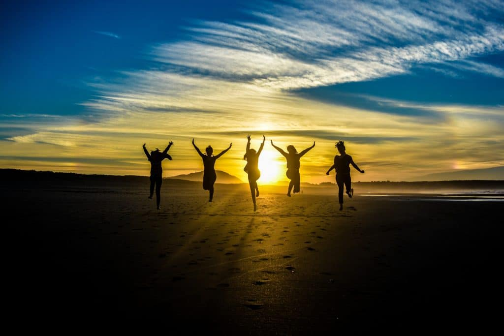 five people jumping with sunset in background